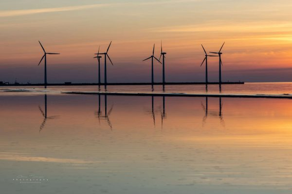 Wind turbines stands tall in the sunset.